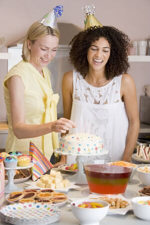 Two women at party putting candles in cake smiling Stock Photo - 3487228