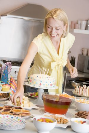 Woman at party getting tart from food table smiling Stock Photo - 3486800