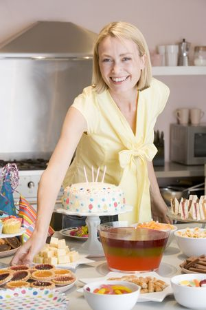 Woman at party getting tart from food table smiling Stock Photo - 3486937