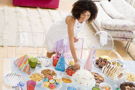 Woman at party fixing cake on food table smiling photo