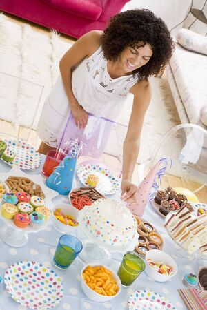 Woman at party putting candles in cake on food table smiling Stock Photo - 3488035