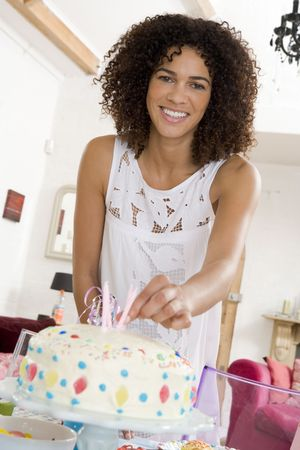 Woman putting candles in cake smiling Stock Photo - 3487036