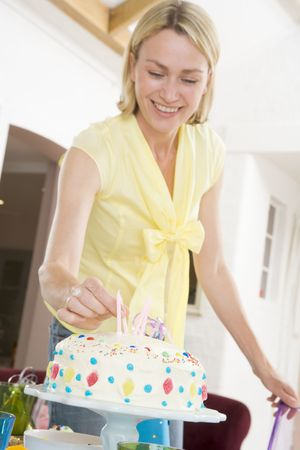 Woman putting candles in cake smiling photo