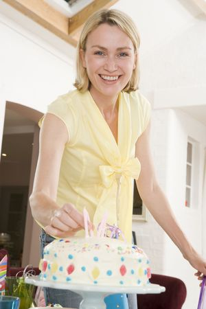 Woman putting candles in cake smiling Stock Photo - 3485967
