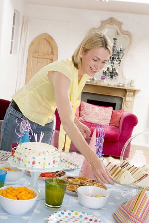 Woman at party setting out food and smiling Stock Photo - 3487015