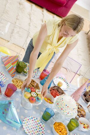 Woman at party setting out food and smiling photo