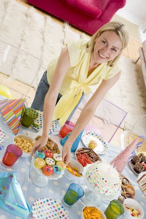Woman at party setting out food and smiling Stock Photo - 3487496