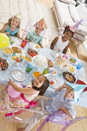 childrens food: Young children at party sitting at table with food smiling
