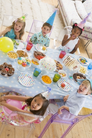 childs birthday party: Young children at party sitting at table with food smiling