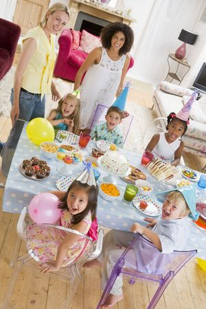 childs birthday party: Young children at party with mothers sitting at table with food smiling Stock Photo