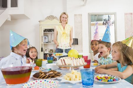 kids food: Young children at party sitting at table with mother carrying cake and smiling