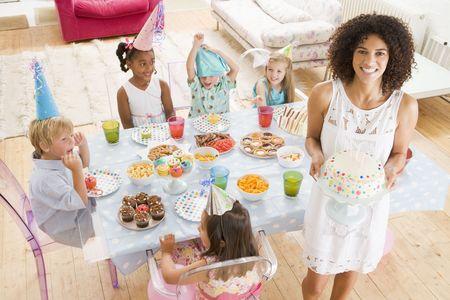 mujer hijos: Los ni�os peque�os a las partes a la mesa sentado con la madre y el desempe�o pastel sonriente  Foto de archivo