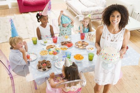 Young children at party sitting at table with mother carrying cake and smiling photo