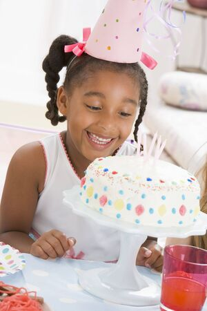 childrens birthday party: Young girl wearing party hat looking at cake smiling Stock Photo