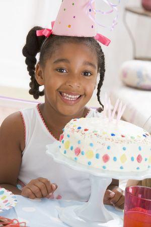 geburtstagskerzen: Junges M�dchen das Tragen Partei Hut mit Kuchen vor ihr l�chelnd