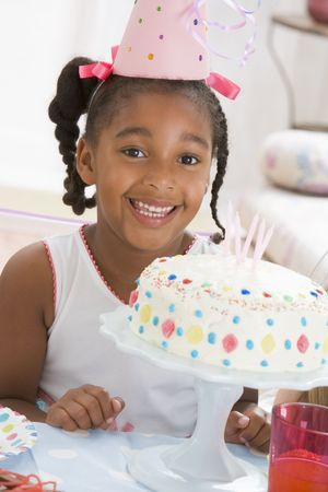 party hat: Young girl wearing party hat with cake in front of her smiling