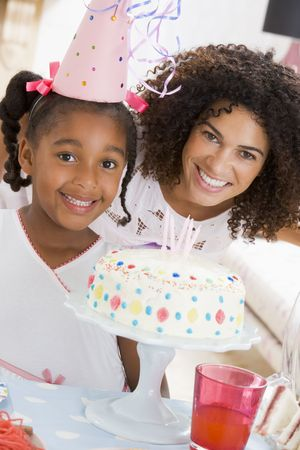childs birthday party: Mother and daughter with birthday cake smiling
