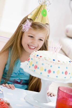 Young girl wearing party hat looking at birthday cake smiling photo