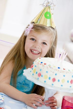 childs birthday party: Young girl wearing party hat with birthday cake smiling Stock Photo