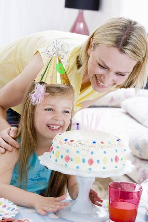 birthday food: Mother and daughter with birthday cake smiling