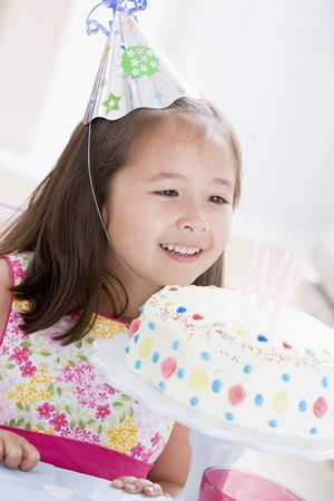 childs birthday party: Young girl wearing party hat looking at birthday cake smiling