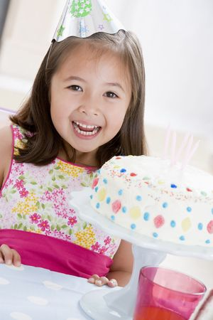 Young girl wearing party hat with birthday cake smiling Stock Photo - 3487121
