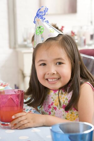 childrens birthday party: Young girl wearing party hat at table smiling