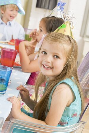 childs birthday party: Young girl at party sitting at table with food smiling