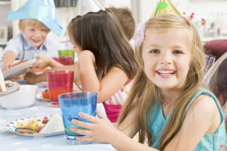 Young girl at party sitting at table with food smiling photo