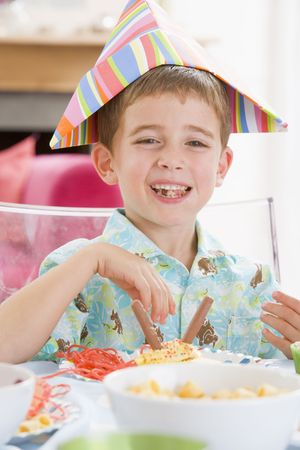 Young boy at party sitting at table with food smiling Stock Photo - 3486758