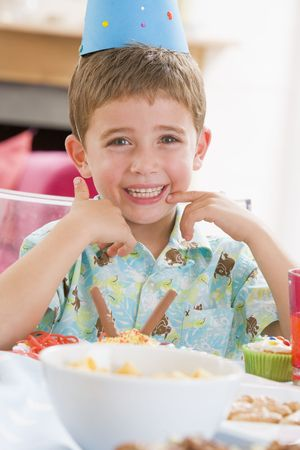 Young boy at party sitting at table with food smiling photo