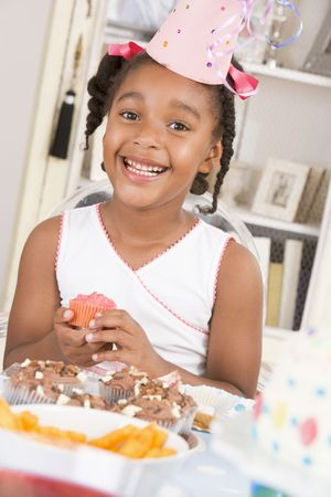 childs birthday party: Young girl at party sitting at table with a cupcake smiling
