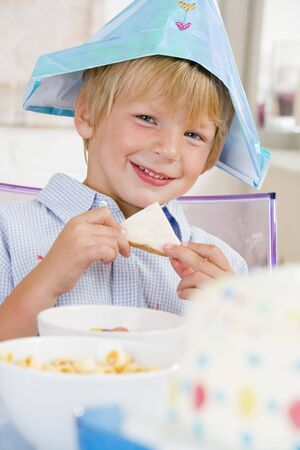 childrens food: Young boy at party sitting at table with a sandwich smiling