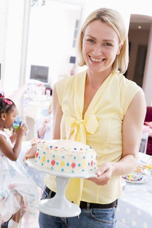 Woman at party holding birthday cake smiling photo