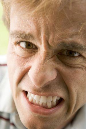 bad temper: Head shot of man scowling
