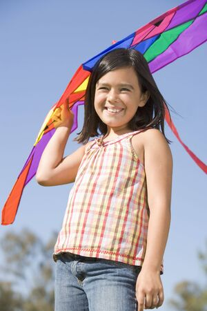 Young girl with kite outdoors smiling photo