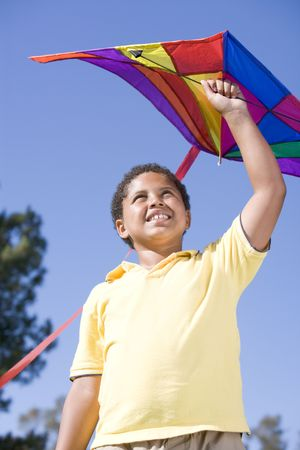 Young boy with kite outdoors smiling photo