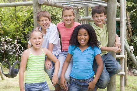 Vijf jonge vrienden op een speelplaats glimlachend