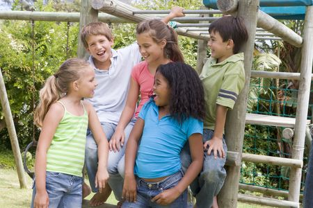 kid sitting: Five young friends at a playground smiling Stock Photo