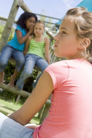cruelty: Two young girl friends at a playground whispering about other girl in foreground Stock Photo