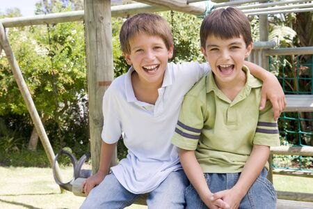 boy standing: Two young male friends at a playground smiling