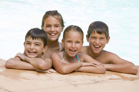 Four young friends in swimming pool smiling photo