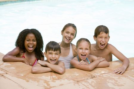 swimming race: Five young friends in swimming pool smiling Stock Photo