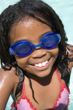 Young girl in swimming pool wearing goggles smiling photo
