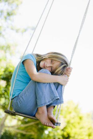 columpio: Ni�a sentada en swing sonriente Foto de archivo