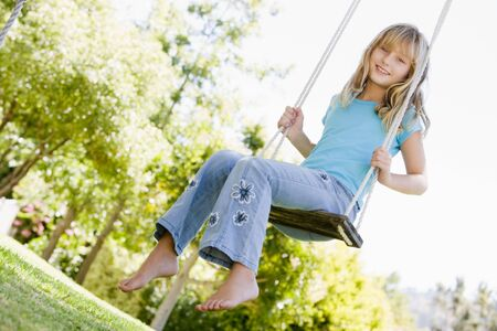 Young girl sitting on swing smiling photo