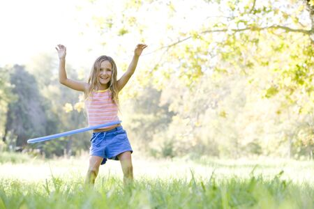 Young girl with hula hoop outdoors smiling photo