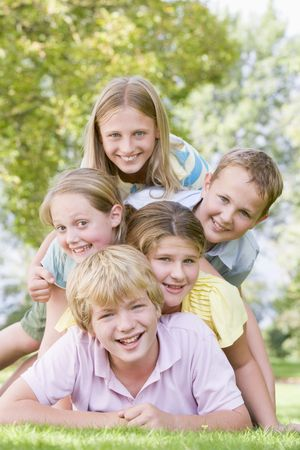 heap up: Five young friends piled on each other outdoors smiling