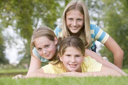 Three young girl friends piled on each other outdoors smiling photo