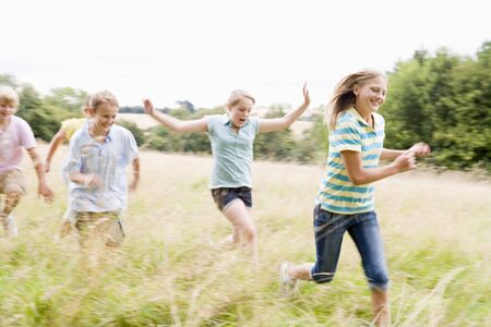 tween boy: Five young friends running in a field smiling